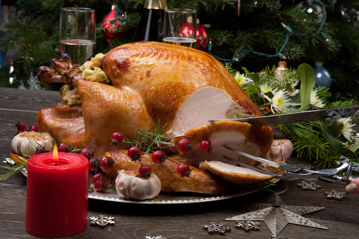 "Carving rustic style roasted Christmas turkey garnished with roasted garlic, lemon, and rosehips. Surrounded with rustic Christmas ornaments, candles, wine, flowers, and Christmas tree in the background.""n"