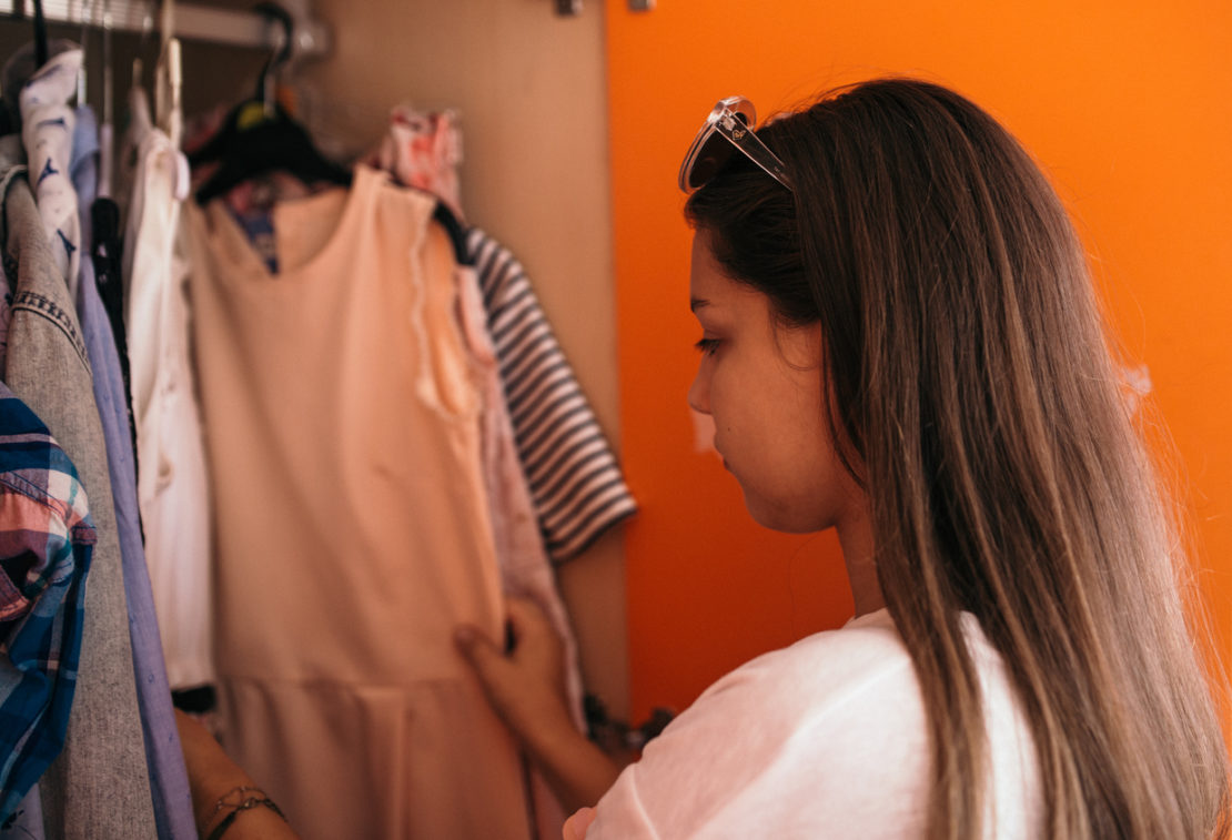 A photo of a teenager selecting what to wear