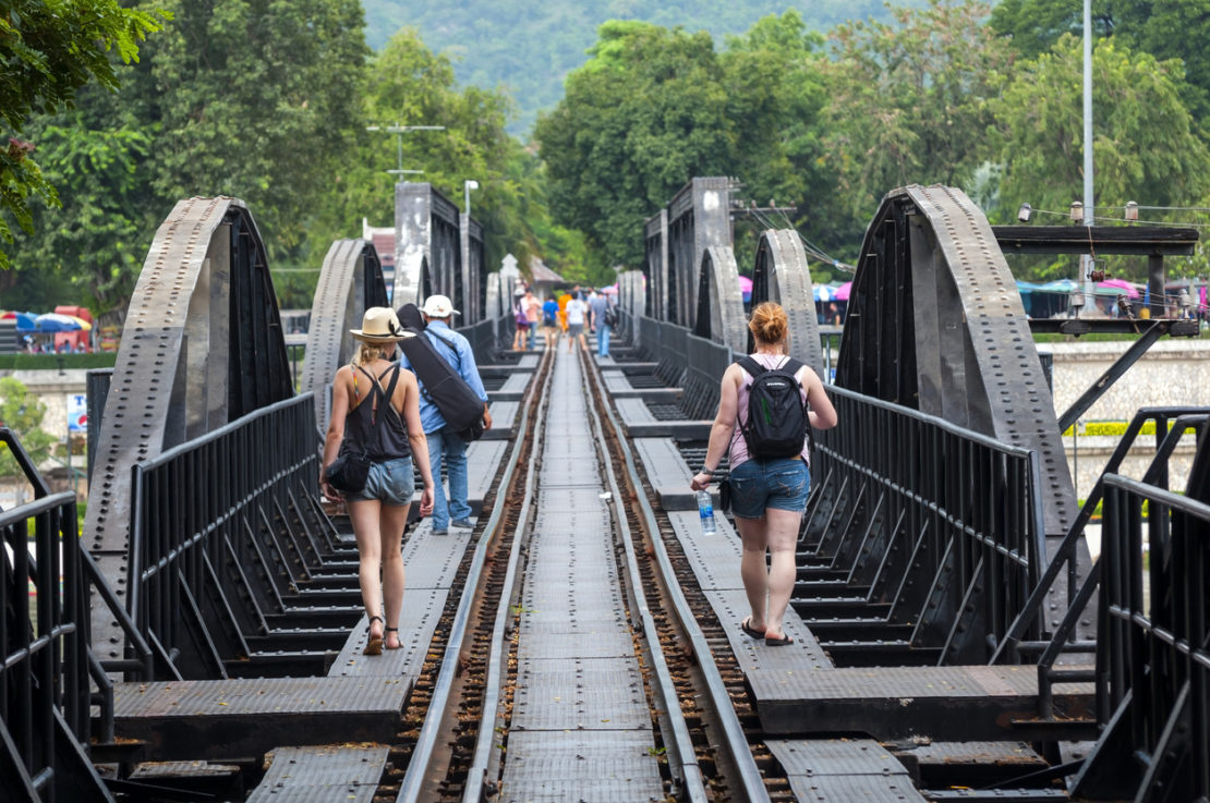 Kanchanaburi, Thailand - October 3, 2011: Among the people walking across the famous Bridge on the River Kwai, built by Allied POW labor during World War II, are two young Western backpackers. The bridge is part of the Death Railway.