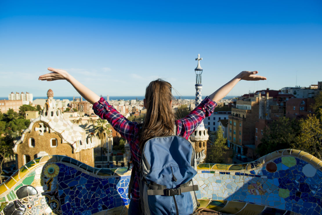 Rear view of young female tourist enjoying the view in Parc Guell in Barcelona, Spain.