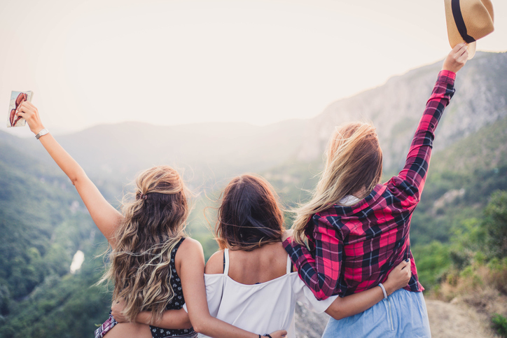 Girlfriends on viewpoint enjoying in nature