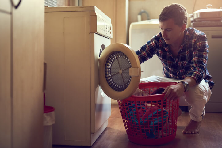 Shot of a young man doing laundry at home